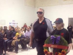 Photo of Ross Martin with a young person carrying a Remembrance Day wreath.